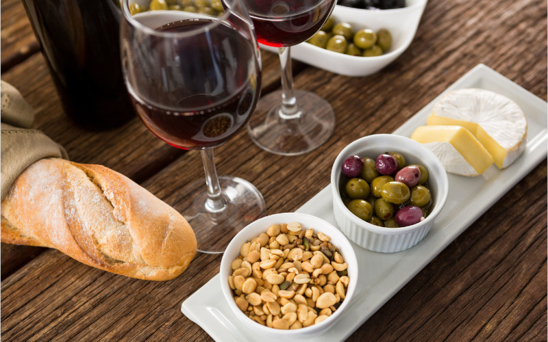 glass of wine bread olives peanuts cheese